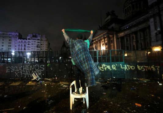 Un homme brandit un mouchoir vert, symbole des partisans du droit à l'avortement, face aux policiers devant le Congrès à Buenos Aires après le vote des sénateurs, dans la nuit du 8 au 9 août.