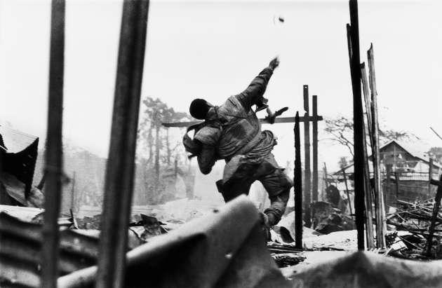 Marine américain lançant une grenade quelques secondes avant d'être blessé à la main gauche par un tir, lors de l'offensive du Têt, sud Vietnam, en février 1968.