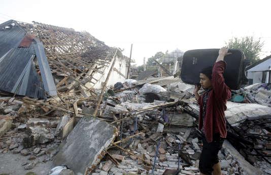 Un homme transporte quelques affaires au milieu des maisons en ruine dans un village, sur l'île de Lombok (Indonésie), le 9août.