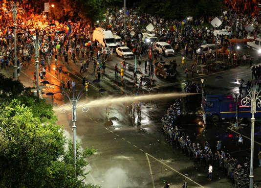 La police utilise un canon à eau contre des manifestants, à Bucarest, en Roumanie, le 10 août.