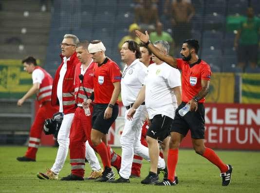 L'arbitre assistant blessé sorti du terrain, à Graz le 9 août.