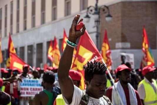 Un ouvrier agricole tient une tomate lors d'une manifestation à Foggia, dans les Pouilles, le 8 août.