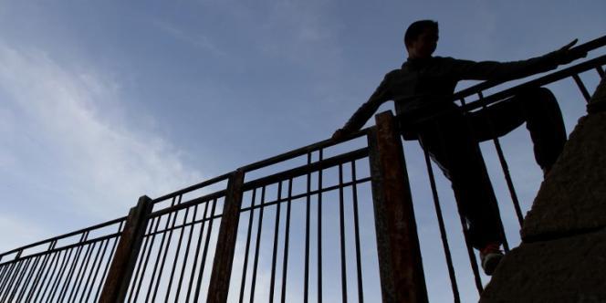 Un jeune Marocain escalade une clôture dans le port de l'enclave espagnole de Melilla, en mai 2017.