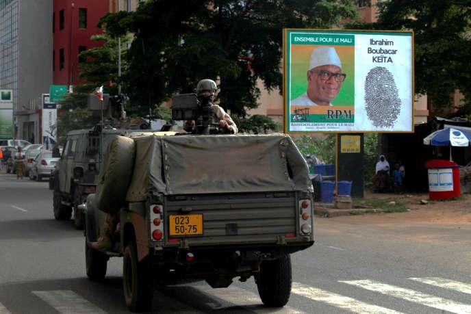 Un convoi des forces de sécurisation devant une affiche électorale du candidat Ibrahim Boubacar Keïta, à Bamako, le 9 août.