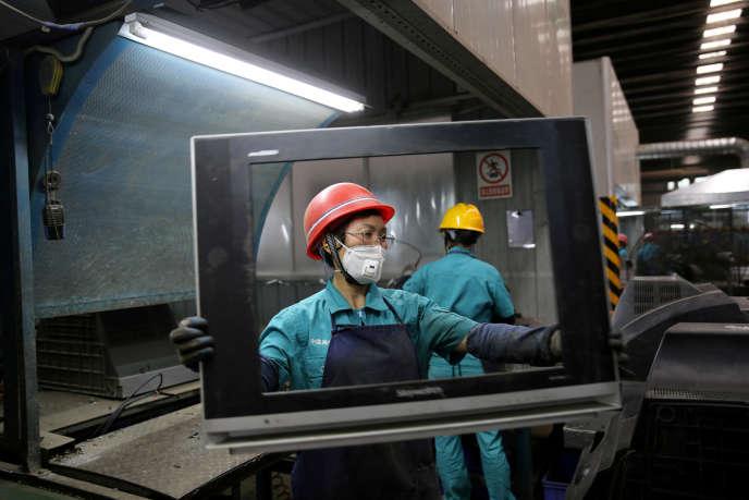 Des travailleurs démantèlent des téléviseurs, à Neijiang, dans la province chinoise du Sichuan, le 11 juin.