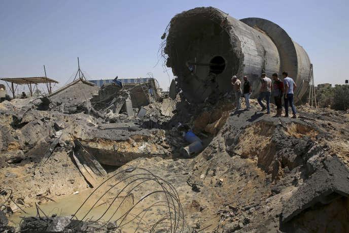Des Palestiniens inspectent les restes d'un centre de distribution d'eau détruit par des frappes israéliennes, le 9 août 2018, à Mughraqa, dans la bande de Gaza.