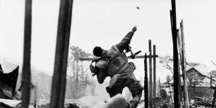 Marine américain lançant une grenade quelques secondes avant d'être blessé à la main gauche par un tir, offensive du Têt, sud Vietnam, février 1968.