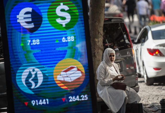 Une femme est assise à côté d'un panneau d'affichage numérique donnant les derniers cours des différentes devises à la Bourse d'Istanbul, le 13 août.