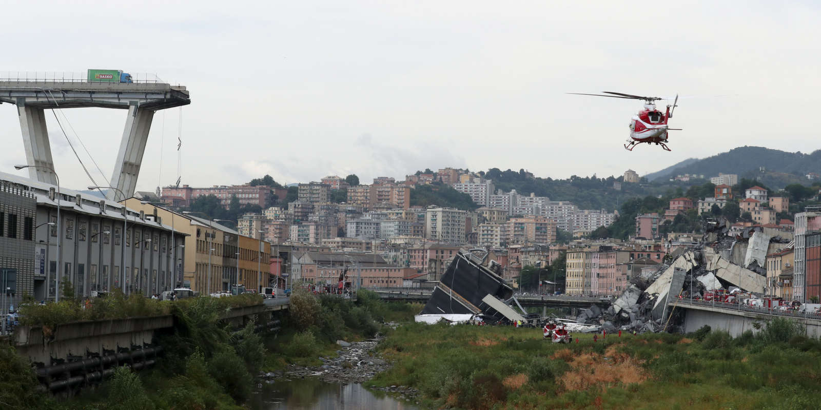 A rescue helicopter flies over the collapsed Morandi Bridge in the Italian port city of Genoa, Italy August 14, 2018. REUTERS/Stefano Rellandini