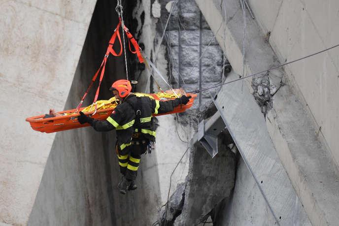 Des sauveteurs ont évacué une femme blessée après l'effondrement du pont à Gênes.