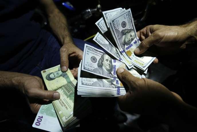 Echanges de devises iraniennes et américaines dans une rue de Téhéran, le 8 août.Depuis février, le rial a perdu 70% de sa valeur face au dollar.