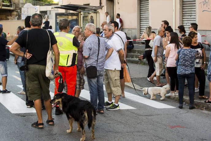 Des habitants évacués attendent de pouvoir récupérer des effets personnels, près du pont effondré, à Gênes, le 15 août.