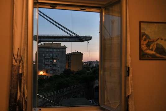 A travers une fenêtre d'un appartement situé sous le pont de l'autoroute de Morandi, à Gênes, le 15 août.