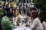 Une manifestation en faveur de la régularisation des sans-papiers passe devant la terrasse d'un restaurant, à Paris, le 2 juin.