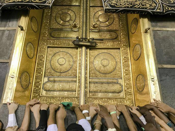 Les pèlerins touchent la porte d'or de la Kaaba, au centre de la Mosquée sacrée de la Mecque, le 17 août.