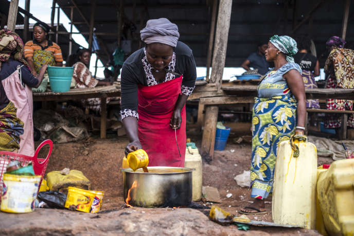 Une femme prépare et vend de l'huile de palme sur le marché de Béni (République démocratique du Congo), le 9 novembre 2016.