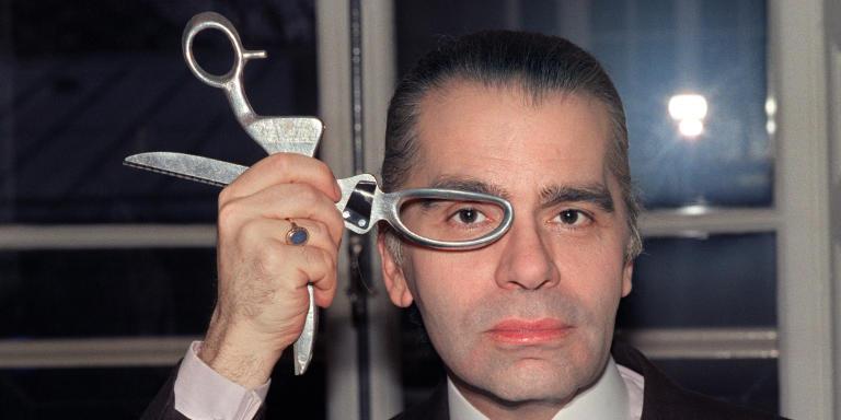 Le couturier Karl Lagerfeld pose avec une paire de ciseaux en mars 1987 dans son atelier de haute couture. German designer Karl Lagerfeld poses with scissors on March 1987 in his fashion studio. / AFP PHOTO / PIERRE GUILLAUD