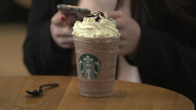 Une consommatrice attablée dans un café Starbucks à Paris.