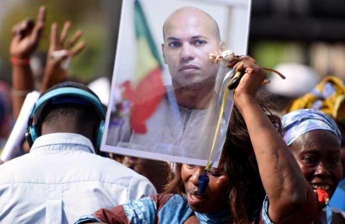 Une femme brandit un portrait de Karim Wade lors d'un rassemblement de l'opposition, à Dakar, en février 2015.