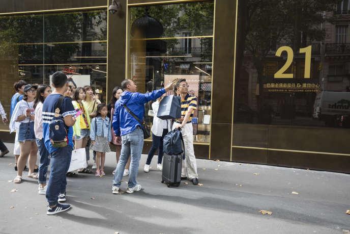 Des touristes asiatiques devant leShopping &Welcome Center, boulevard Haussmann à Paris.