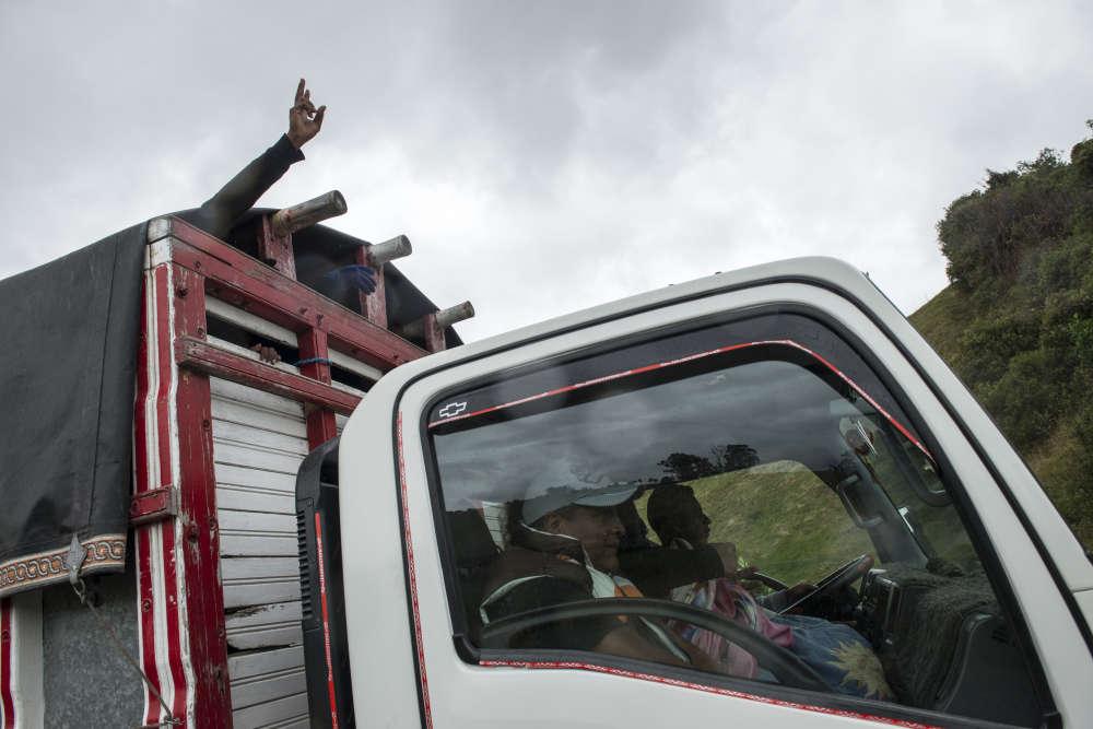 Des marcheurs ont trouvé de la place pour voyager à l'arrière d'une camionnette.