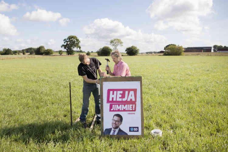 Dans l'un de ses champs, l'agriculteur Stig Ottosson, «Sverigedemokrat» convaincu, installe avec son fils un panneau de campagnemontrant le patron du SD, Jimmie Akesson.