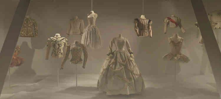 Entrez dans le monde des princes et des princesses: un monde hors du temps, dominé par le blanc et le pastel rehaussésd'éclats d'or et de strass. Suspendus dans l'air ou posés sur des socles, les costumes présentés dans cette vitrine qui ouvre l'exposition à Moulins, s'inspirent de l'imaginaire de la féérie du XIXe siècle. Les pourpoints serrés masculins s'accordent en majesté à la finesse des tailles féminines, et nul ne doute, en les voyant, qu'une baguette magique princière viendra réveiller une princesse endormie.