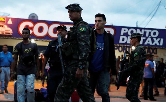Des soldats brésiliens contrôlent les passeports à la frontière avec le Venezuela, le 19août.