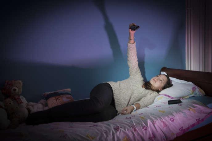 Adolescente dans sa chambre et sur son lit avec son appareil photo et ses peluches.Extrait de la série « L'Antre de la jeunesse» (2015-2017).
