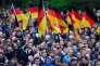 "Demonstrators hold flags of Germany during a protest organised by the right-wing populist ""Pro Chemnitz"" movement, the far-right Alternative for Germany (AfD) party and the anti-Islam Pegida movement, on September 1, 2018 in Chemnitz, eastern Germany. The demonstration was organised in a reaction to a knife killing, allegedly by an Iraqi and a Syrian, that set off anti-immigrant mob violence. / AFP / John MACDOUGALL"