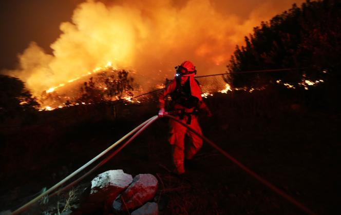 A firefighter works as the Holy Fire burns near homes on August 9, 2018 in Lake Elsinore, California.