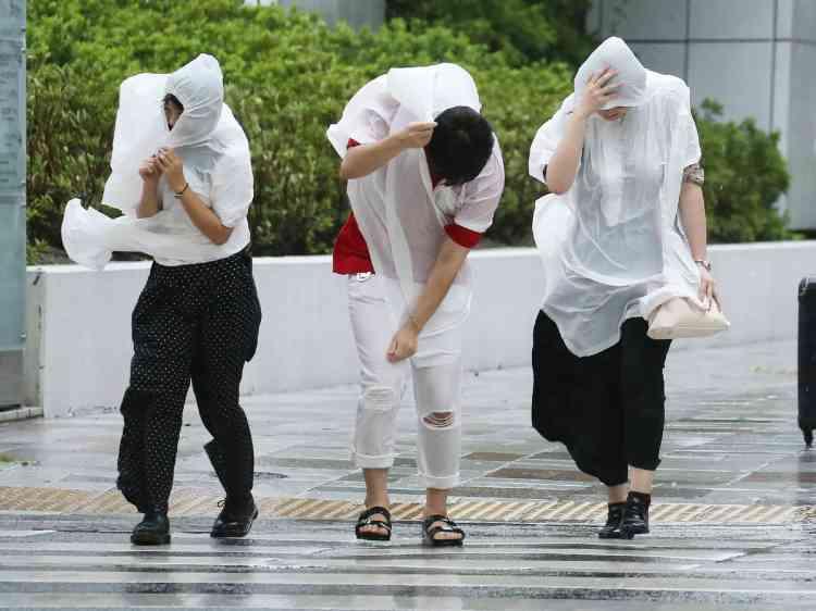 Des piétons à Nagoya.De nombreux habitants de zones inondables ou susceptibles d'être touchées par des coulées de boue ont été appelés à quitter leur logement.