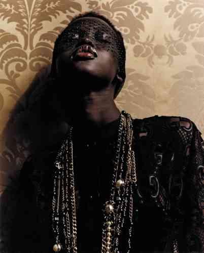 Blouse en dentelle et broderie macramé imprimées GG, Gucci. Colliers en chaîne et perles, Chanel. Masque Le mystérieux en dentelle, tulle et strass, Maison Close.