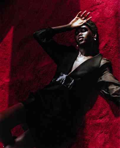 Robe décolletée à manches longues en organza et ceinture nœud, Emporio Armani. Boucles d'oreilles nœud en argent avec perle grise et chaîne, Louis Vuitton.