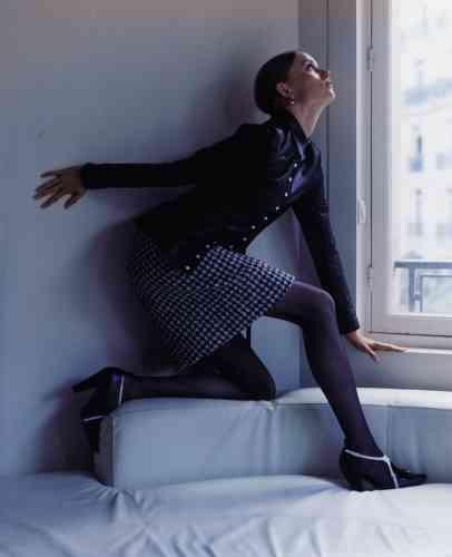 Chemise en cuir, jupe en tweed imprimé pied-de-poule, chaussures en cuir et boucles d'oreilles nœud en argent avec perle grise et chaîne, Louis Vuitton. Collants voile transparent, Wolford.