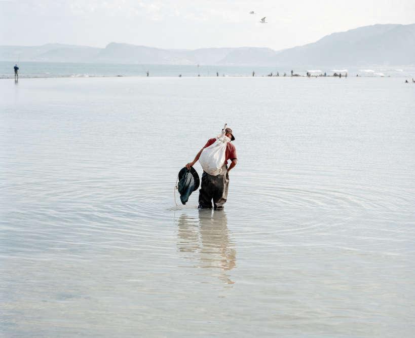 «Andrew, chasseur de vers au pavillon Strandfontein. Le Cap, Afrique du Sud, 2018.» Un homme cherche des vers dans le bassin de marée peu profond du pavillon Strandfontein pour les vendre ensuite aux pêcheurs locaux.