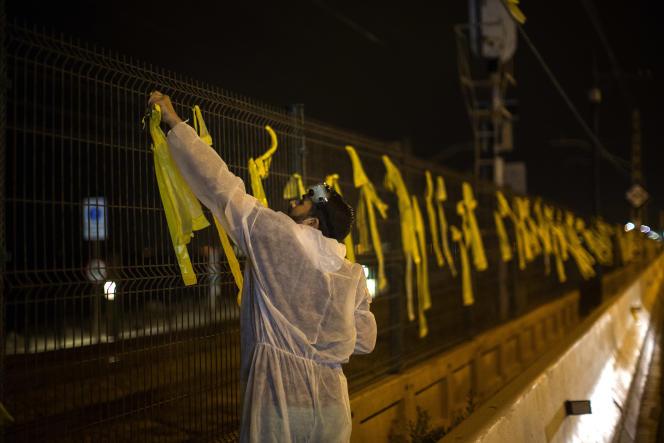 Une personne enlevant les rubans jaunes accrochés par des militants indépendantistes à Premia del Mar, près de Barcelone.