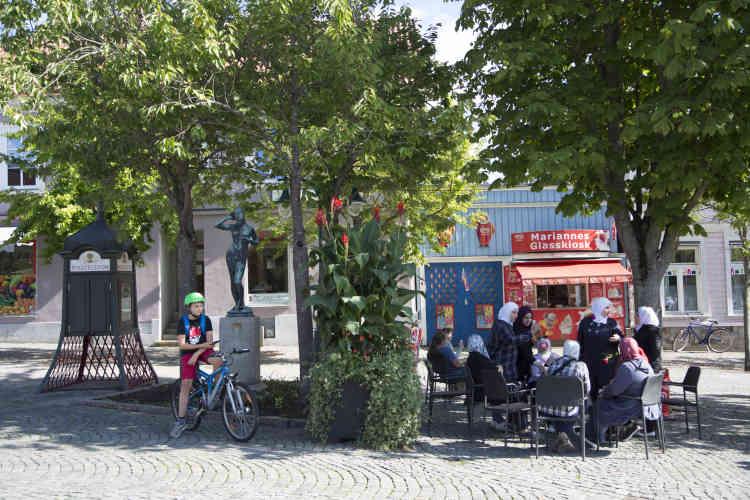 Sur la place de Ronneby, dans le comté de Blekinge, au sud de la Suède, des femmes mangent des glaces en profitant de la fin de l'été. Depuis 2015, la commune de 28 000 habitants a accueilli 2 400 réfugiés.