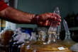 Orestes Estevez contrôle un préservatif utilisé pour la fermentation du vin, à La Havane, Cuba, le 16 mai 2018.