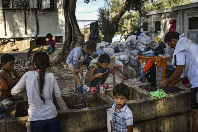 Des migrants à l'extérieur du camp migratoire de Moria, sur l'île de Lesbos, en Grèce, le 5 août.