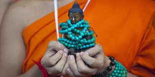 Un moine bouddhiste thaï portant une statue du Bouddha, à Dharamsala, en Inde, en 2018.