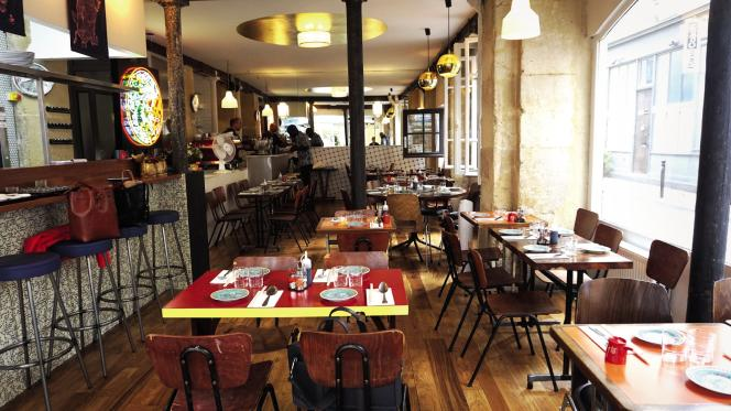 Le restaurant Double Dragon dans son décor pop avec un comptoir de bar pavé de dominos et un néon à l'effigie du jeu vidéo.