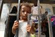 Une petite fille devant la grille d'une école où elle s'est réfugiée avec sa famille après avoir été évacuée d'un village voisin, près de Hodeïda, au Yémen, enjuin.