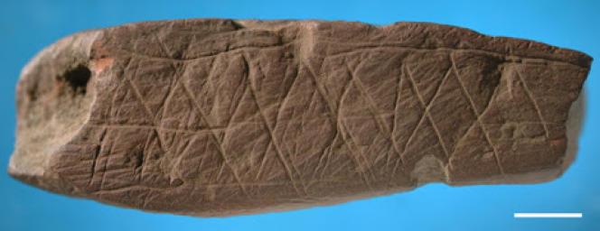 Morceau d'ocre gravé d'un motif abstrait découvert dans la grotte de Blombos, dans la même couche archéologique qui a livré le fragment de silcrète portant le dessin.