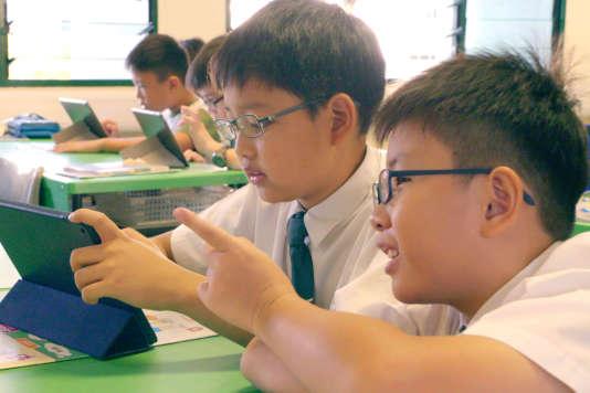 Des enfants apprennent à l'aide d'une tablette.