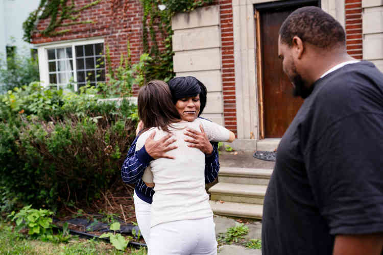 Michelle Berry et son fils Clark accueillent, le 13 septembre, Michele Oberholtzer, membre de l'association United Community Housing Coalition, qui les a aidés àc onserver leur maison à Detroit.