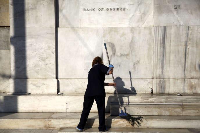 Une employée nettoie l'entrée de la Banque de Grèce, à Athènes, en juillet 2015.