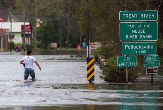 Un homme tente de traverser un pont submergé à Pollocksville, en Caroline du Nord, le16septembre.