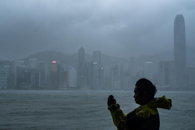 Un homme prend une photo à Hongkong, en Chine, à l'approche du supertyphon Mnagkhut, le 16 septembre.