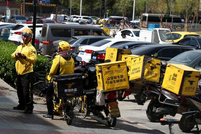 Des livreurs de repas de Meituan, à Pékin, le 11 avril.